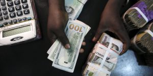 File photo of a trader changing dollars with naira at a currency exchange store in Lagos